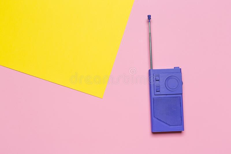 Violet retro radio receiver on a pink yellow pastel background. Top view stock photos