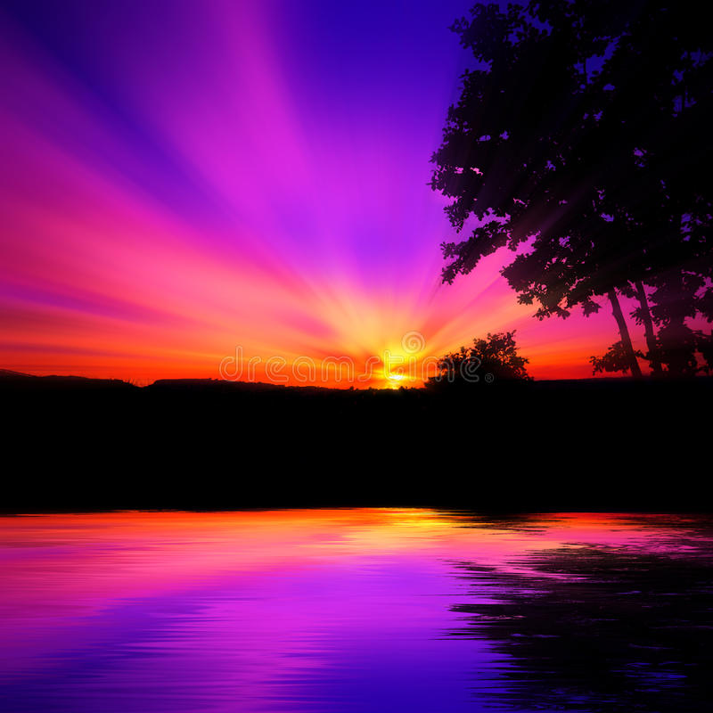 Violet sunset over water. Sunrise or sunny set in hues of purple and orange over water with silhouette of trees stock image
