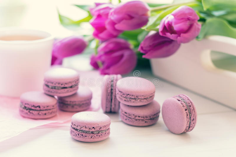 Violet sweet delicious macaroons and fresh tulips royalty free stock photography