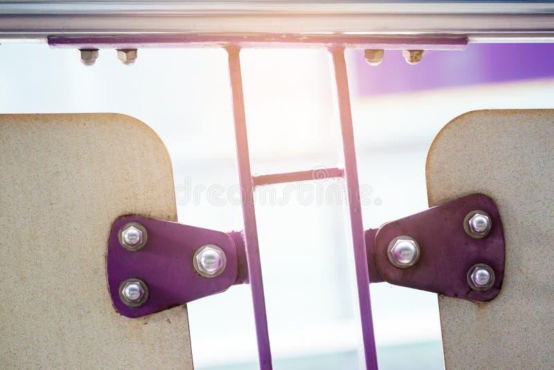 A violeta pintou folhas de metal prendidas com parafusos e o NU inoxidável imagem de stock royalty free