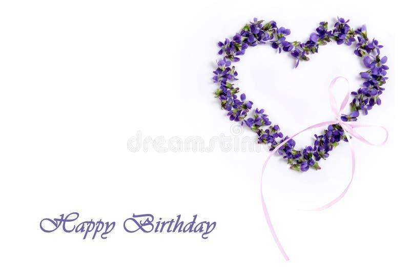 Violetas delicadas de la primavera en la forma de un corazón en un fondo blanco Feliz cumpleaños imagen de archivo