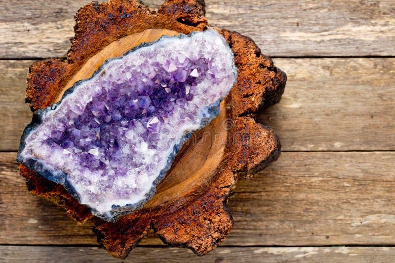 Violetkleurige kristalgeode op dwarsdoorsnede van houtlogboek met woode royalty-vrije stock afbeeldingen
