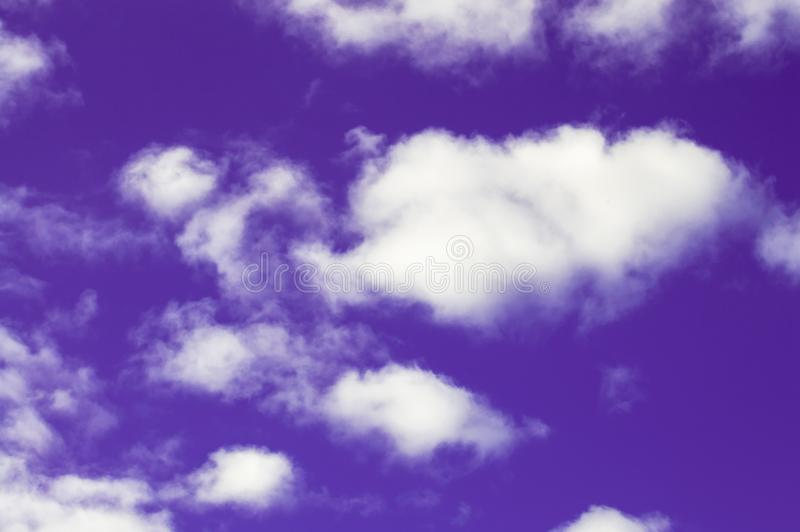 Violett himmel och vita moln royaltyfri foto