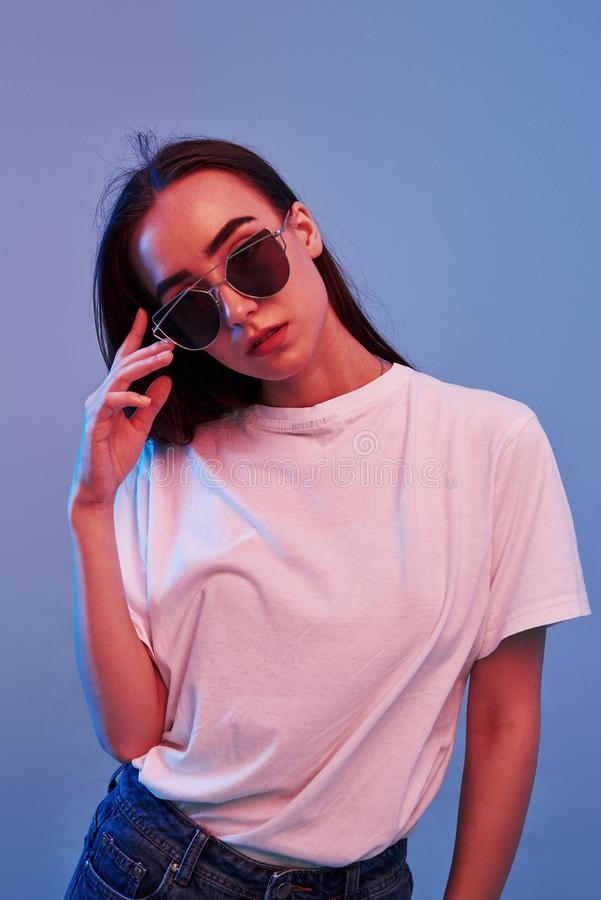 Violett-Hintergrund Studio-Shooting drinnen mit Neonlicht Portrait des schönen jungen Mädchens stockfotos