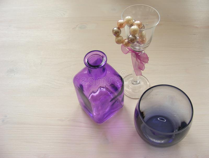 Violett och purpurfärgad exponeringsglas- och pärlasmyckenhalsband på sjaskig trävit bakgrund för kort med copyspace royaltyfria bilder