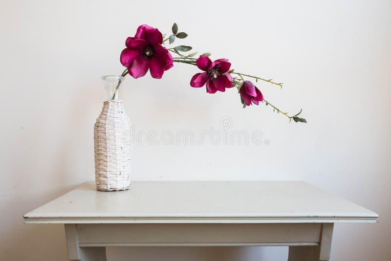 Violette bloemen in witte vaas op houten lijst uitstekend ontwerp stock afbeeldingen