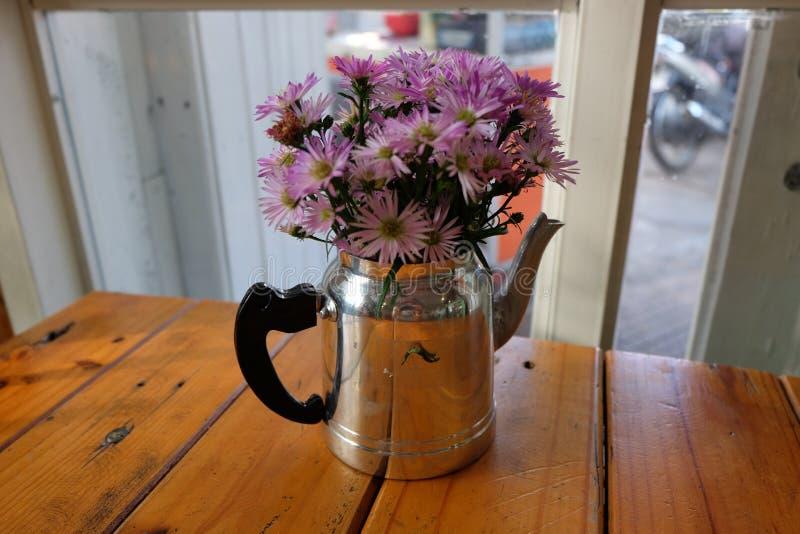 Violette Blumen in einem kleinen Metallteetopf lizenzfreie stockbilder