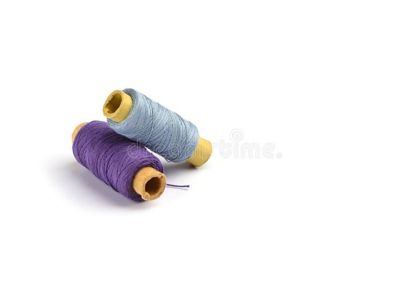 Violette de coton et fils bleu-clair sur la douille de carton pour la machine à coudre image libre de droits