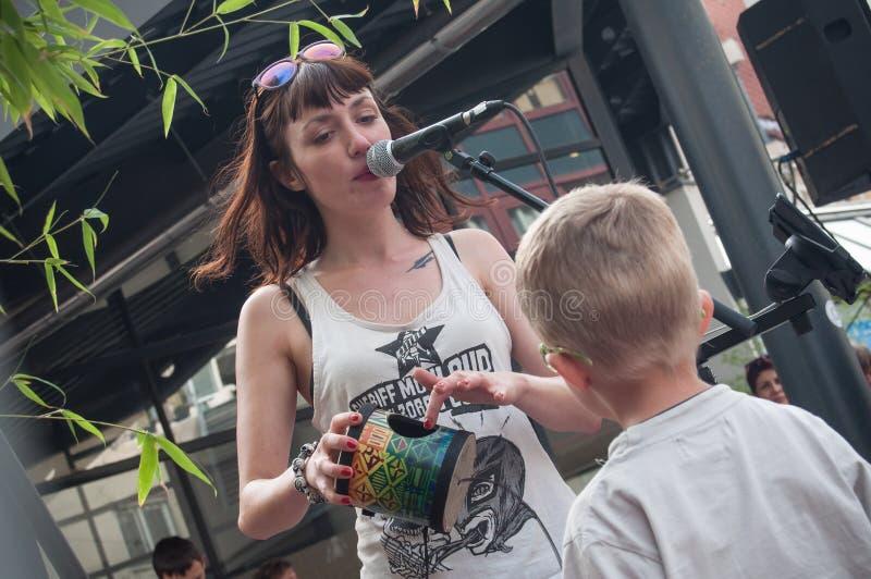 Violette Deadwood com a criança do público durante o festival da cena da rua fotografia de stock