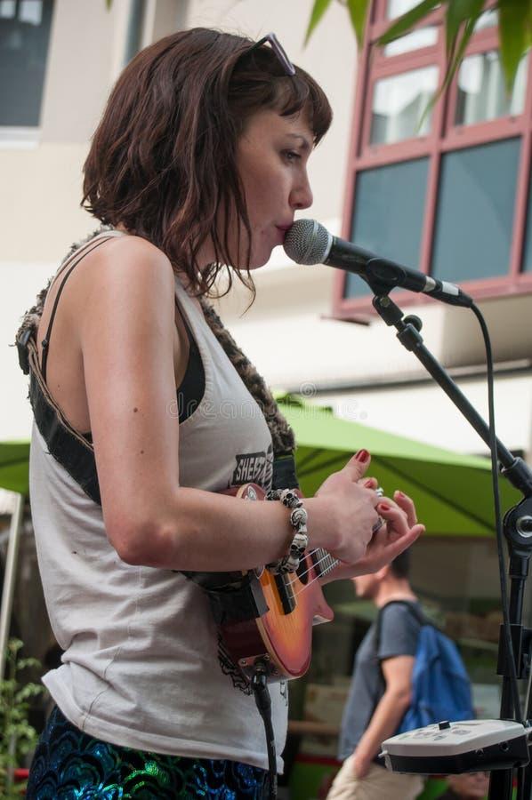 Violette Deadwood som sjunger med gitarren under gataplatsfestivalen arkivfoton