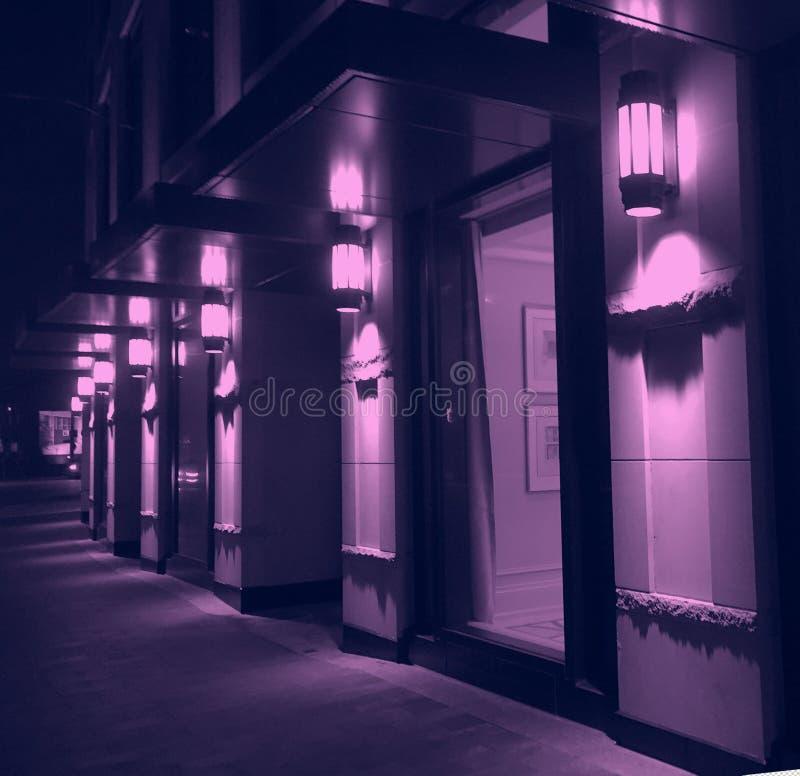 Violette nachtverlichting van moderne stad de bouwvoorgevel royalty-vrije stock afbeeldingen