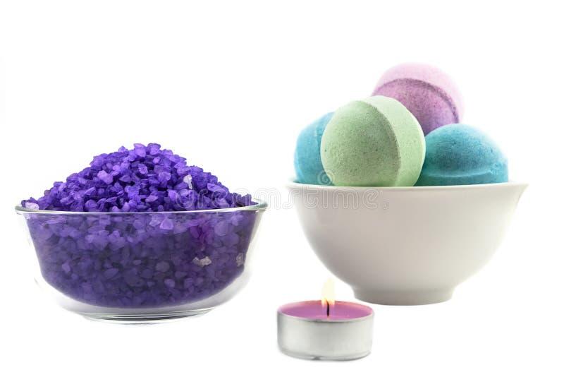 Violette Salz wiih Kerze- und Badkugeln stockbild