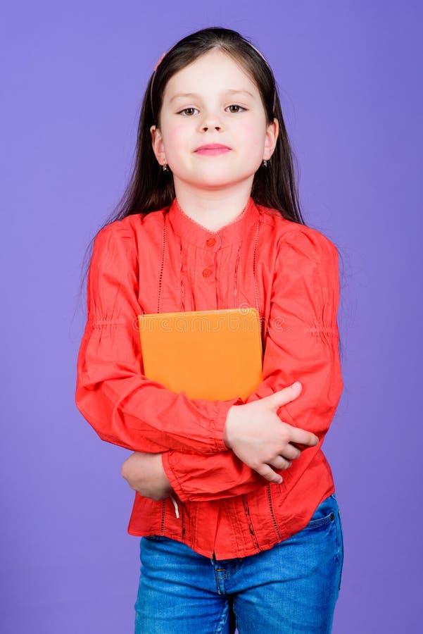 Violetter Hintergrund des M?dchengriff-Buches Kindershowbuch Buchkonzept Kluge Zitate Literaturclub Entwicklung und Ausbildung lizenzfreie stockfotos