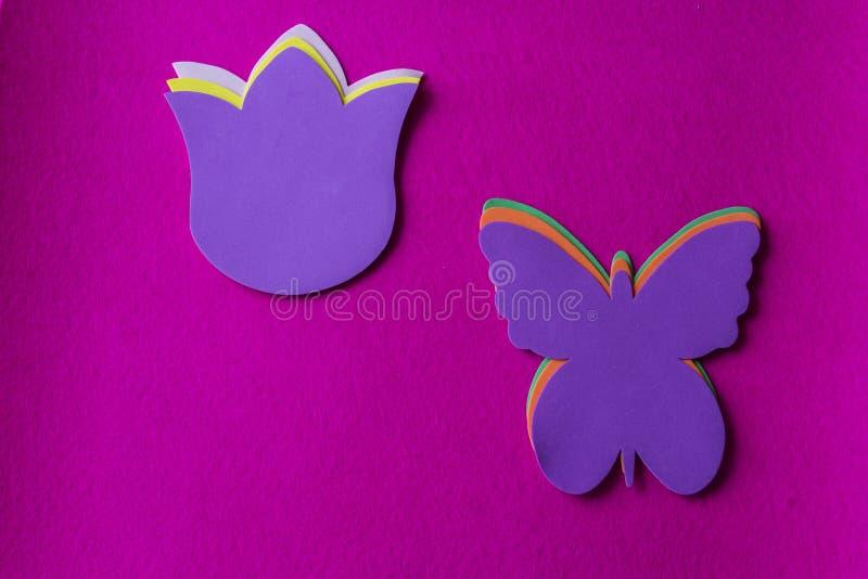 Violetter Schmetterling und Blume gemacht vom weichen Material auf pinkfarbenem Hintergrund lizenzfreie stockfotografie