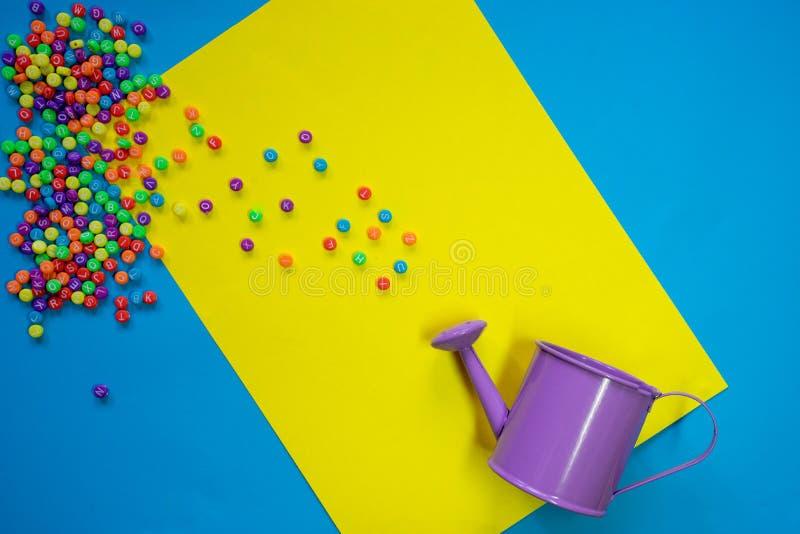 Violetter Topf der flachen Schicht, der die Buchstaben des englischen Alphabetes, knowled wässert lizenzfreies stockfoto