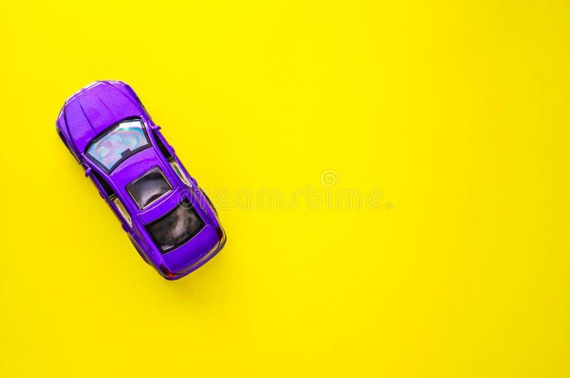 Violettes Modell des Spielzeugs des Autos auf gelbem Hintergrund mit Raum für Text lizenzfreies stockbild