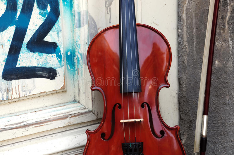 The violin. Detail, violin leaning on the old wooden door royalty free stock image