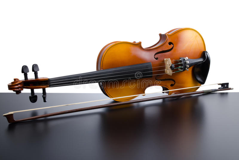 Violin. On top of dark table partially isolated on white background stock images