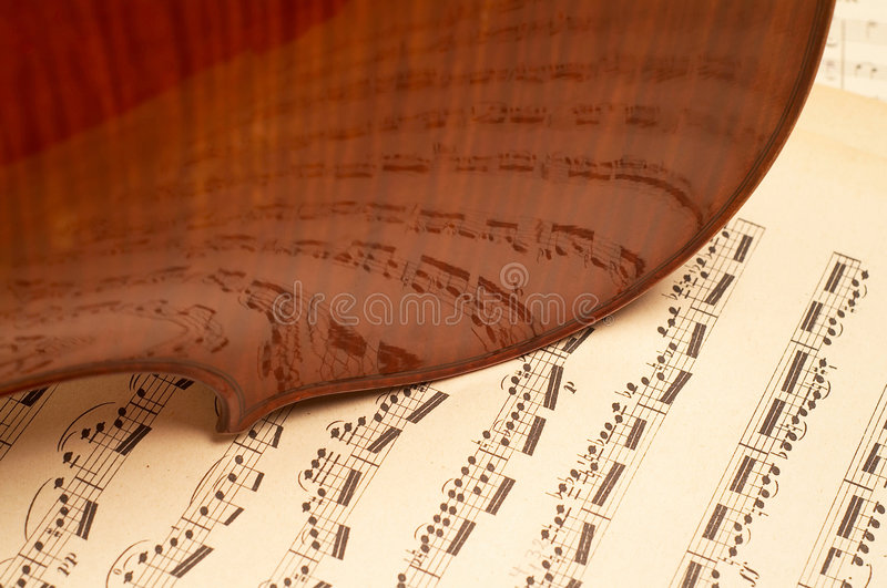 Violin. E close-up over music notes royalty free stock photo