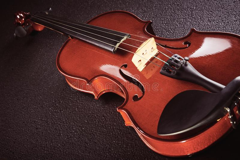 Violin on black background. Part of a violin on a black background with hard light stock images