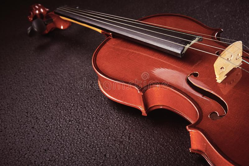 Violin on black background. Part of a violin on a black background with hard light stock photo