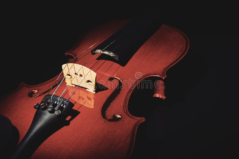 Violin on black background. Part of a violin on a black background with hard light royalty free stock photography