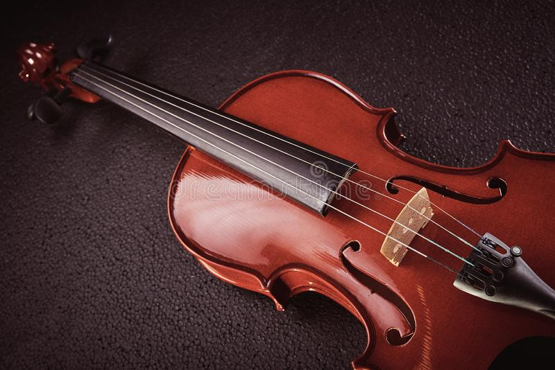 Violin on black background. Part of a violin on a black background with hard light stock photography