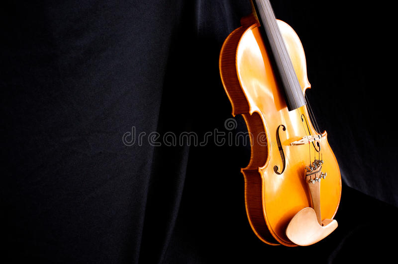 Violin body leaning on black. A beautiful violin is leaning against a black backdrop at slight angle with copy space royalty free stock photos