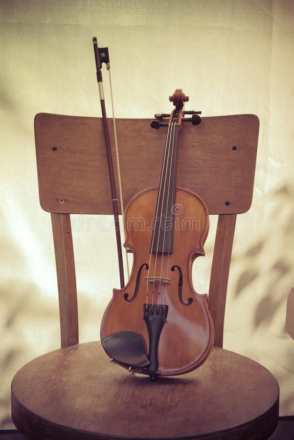 Violin and bow, stand on an old wooden chair. Concept art. Vintage style toned photo. Violin and bow, stand on an old wooden chair. Concept art. Retro style stock images