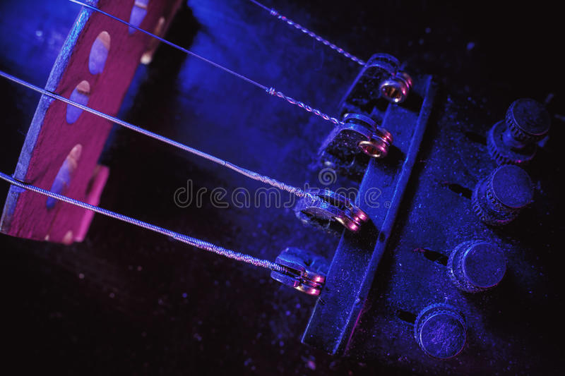 Violin Bridge and Fine Tuners. Studio composition of an old dusty violin, blue and purple illumination from aside, closeup view on bridge and fine tuners stock image