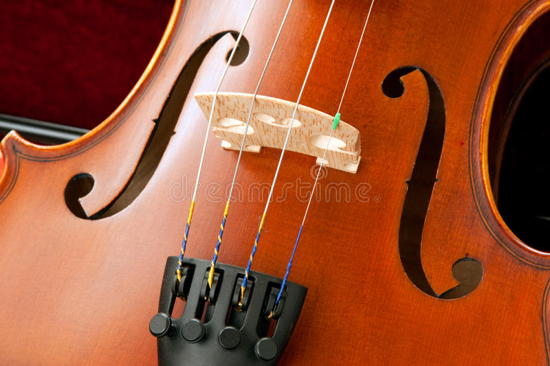Violin Bridge and Srings. Close up of a violin bridge, strings, tailpiece, fine tuner and f holes royalty free stock photo