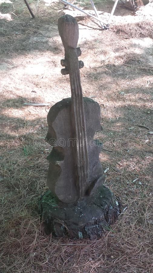 A Violin carved out of a Tree Stump. A Violin carved out of a stump in the Wheatland festival campgrounds in Michigan royalty free stock images