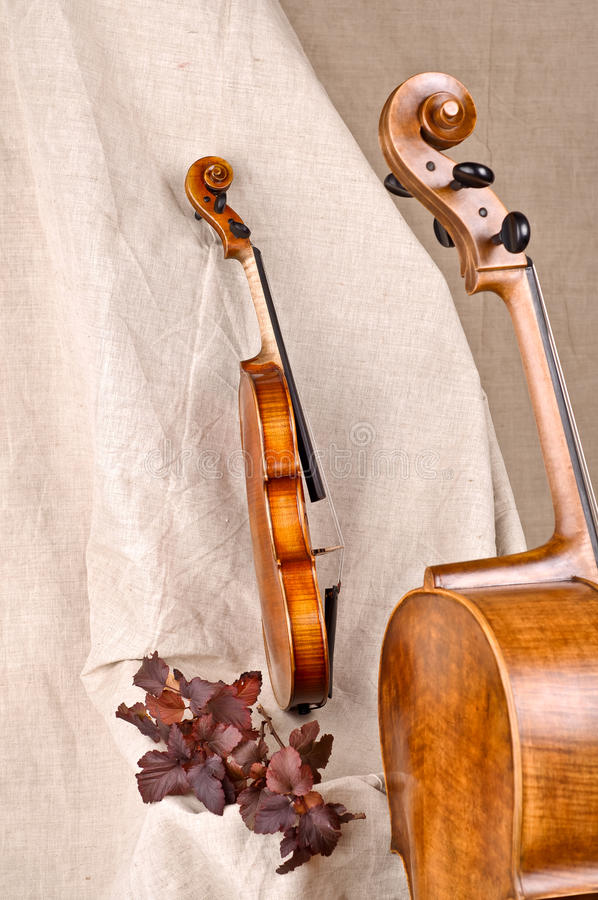 Violin and cello on beige background. Isolated violin and cello on beige background stock photo