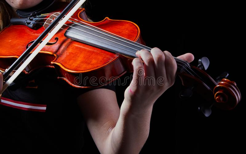 Violin classic musical instrument. Classic player hands on a black background. Details of violin playing. Orchestra, violinist, symphony, concert, musician stock image
