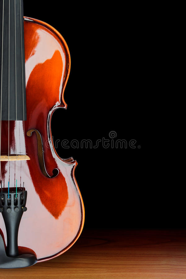 Violin. Close up of shiny violin on wooden table, isolated on black background, with clipping path royalty free stock image