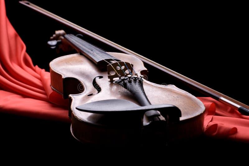 Violin with fiddlestick. Old violin with fiddlestick on folded scarlet silk on black background stock photography