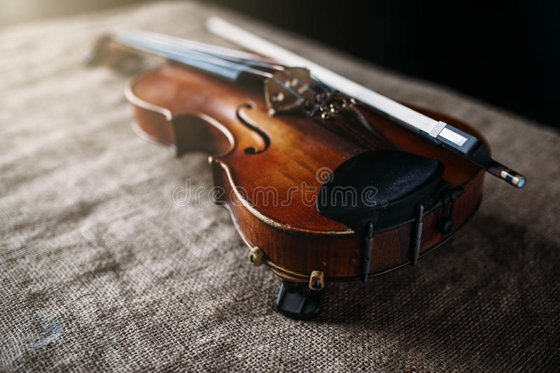 Violin, fiddlestick and bowtie, canvas background. Violin, fiddlestick and bowtie on grunge canvas background, closeup view royalty free stock photo