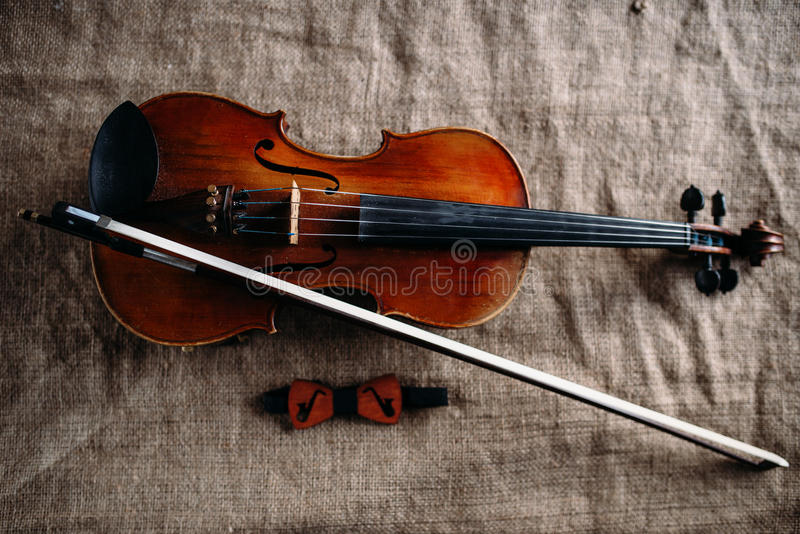 Violin, fiddlestick and bowtie, canvas background. Violin, fiddlestick and bowtie on grunge canvas background, closeup view stock photos