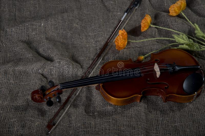 Violin, fiddlestick and bowtie, canvas background. Violin, fiddlestick, notes and bowties closeup.Violin and bow on jute sack background stock images