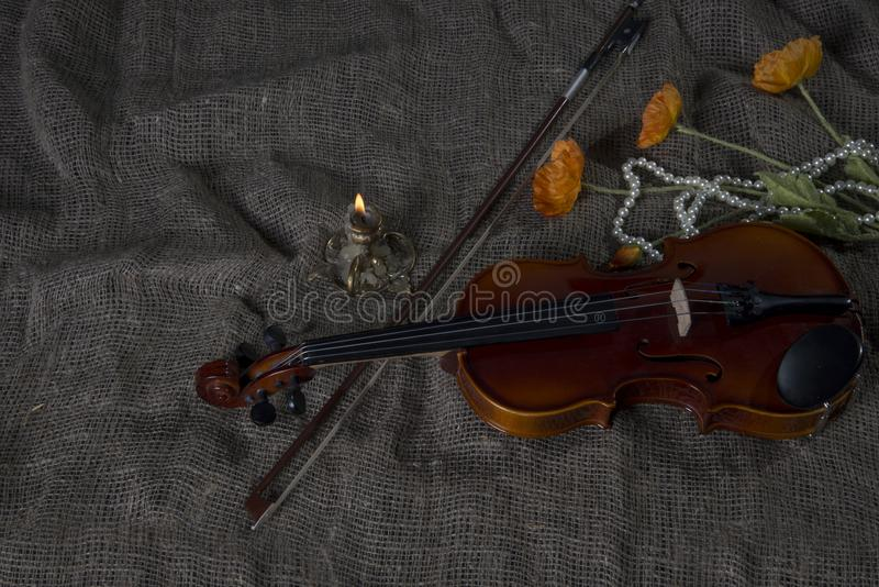 Violin, fiddlestick and bowtie, canvas background. Violin, fiddlestick, notes and bowties closeup.Violin and bow on jute sack background stock image