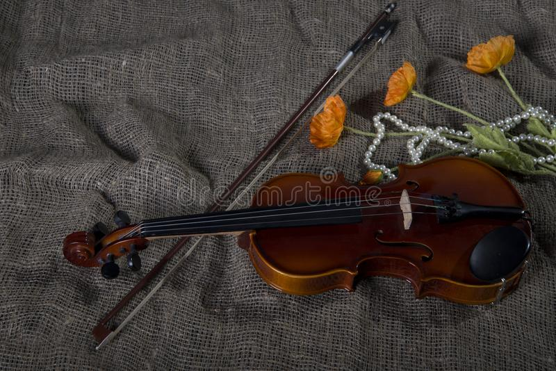 Violin, fiddlestick and bowtie, canvas background. Violin, fiddlestick, notes and bowties closeup.Violin and bow on jute sack background royalty free stock image
