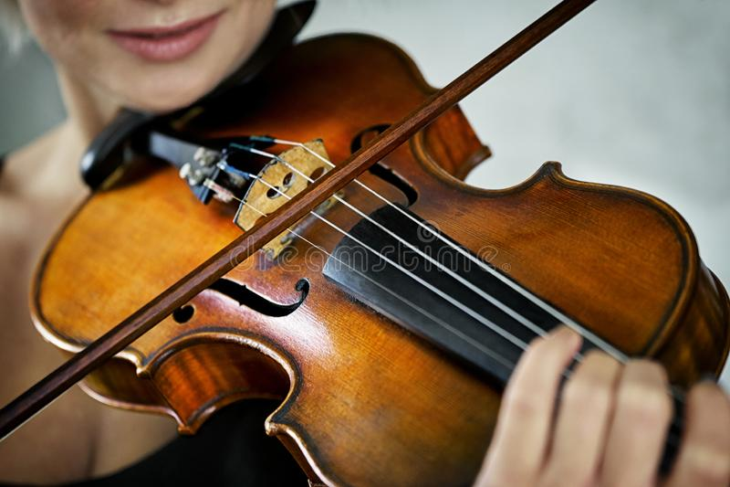Violin and a fiddlestick in hands of a young female violinist royalty free stock photography