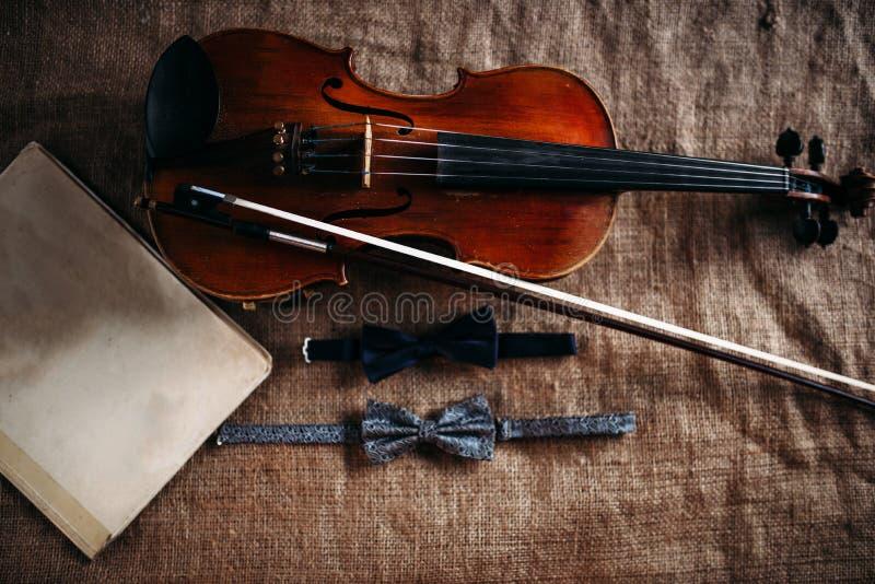 Violin, fiddlestick, notes and bowties closeup. Violin, fiddlestick, notes and bowties on grunge sack texture, closeup view stock images
