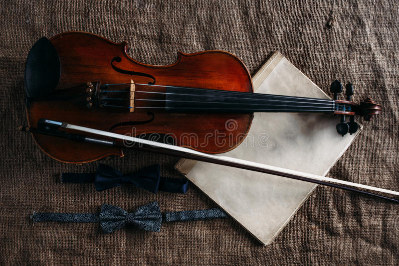Violin, fiddlestick, notes and bowties closeup. Violin, fiddlestick, notes and bowties on grunge sack texture, closeup view royalty free stock images