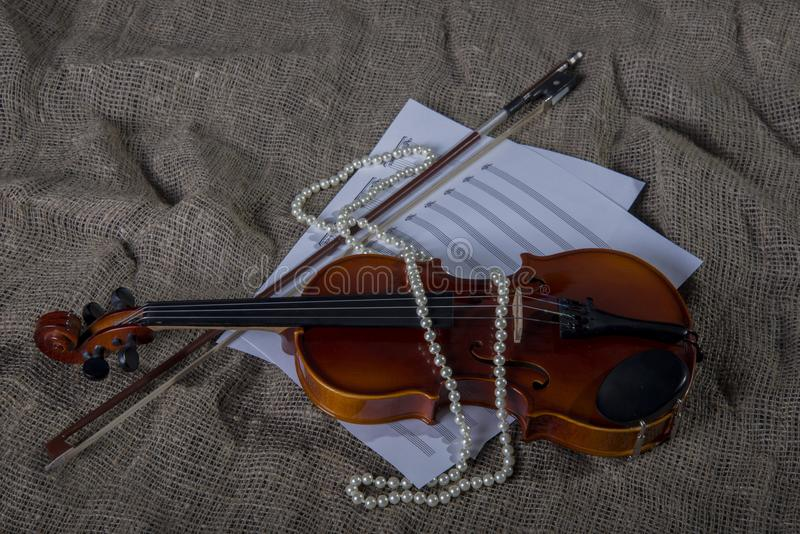 Violin, fiddlestick and bowtie, canvas background. Violin, fiddlestick, notes and bowties closeup.Violin and bow on jute sack background stock photography
