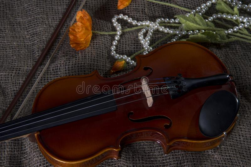Violin, fiddlestick and bowtie, canvas background. Violin, fiddlestick, notes and bowties closeup.Violin and bow on jute sack background royalty free stock photos