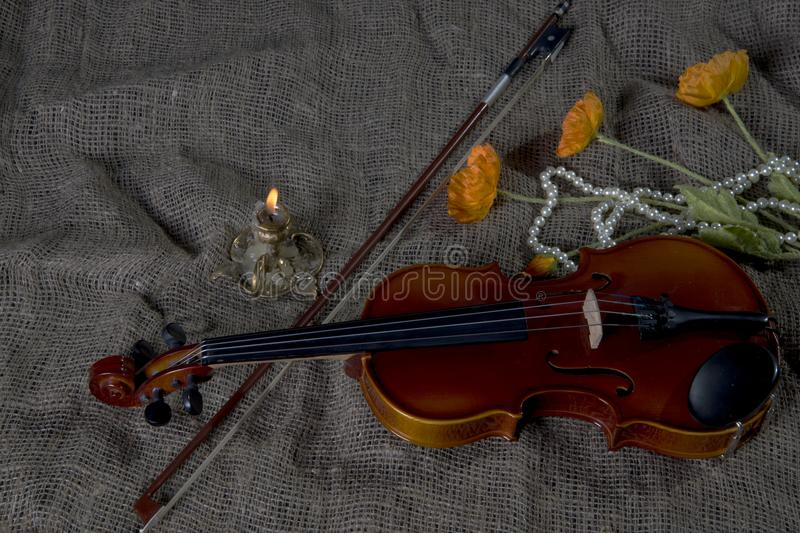 Violin, fiddlestick and bowtie, canvas background. Violin, fiddlestick, notes and bowties closeup.Violin and bow on jute sack background stock photos