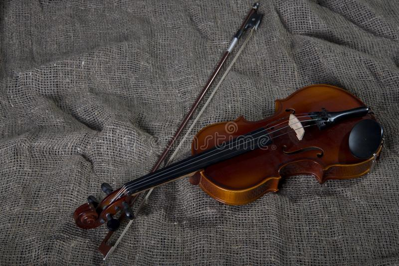 Violin, fiddlestick and bowtie, canvas background. Violin, fiddlestick, notes and bowties closeup.Violin and bow on jute sack background stock photo