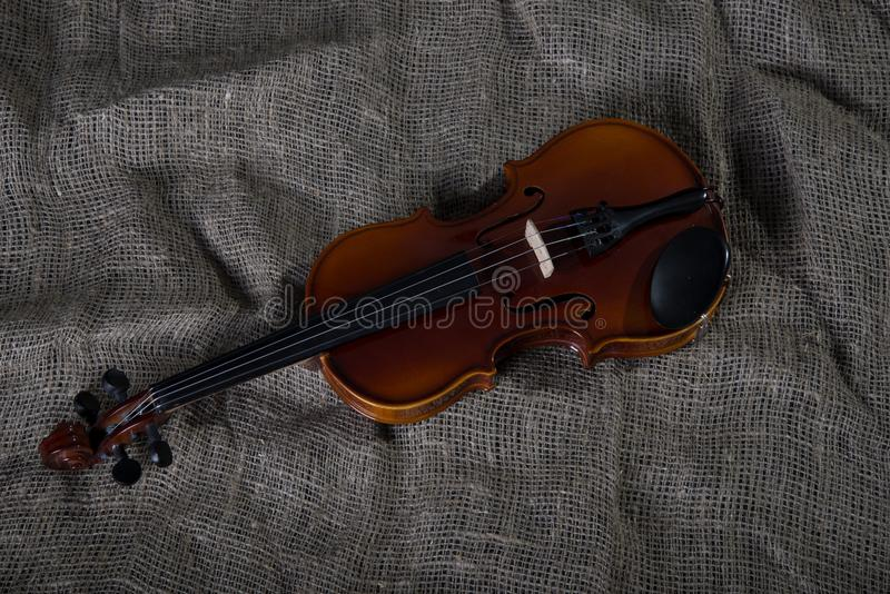 Violin, fiddlestick and bowtie, canvas background. Violin, fiddlestick, notes and bowties closeup.Violin and bow on jute sack background royalty free stock photo