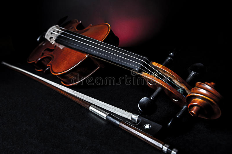 Violin with fiddlestick. Standing violin with a fiddlestick , dark background royalty free stock image